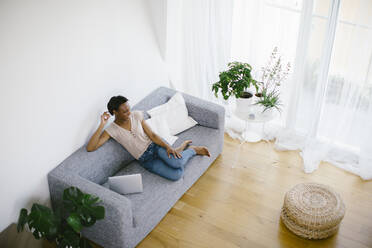 Smiling woman sitting on couch at home with laptop - SODF00028