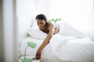 Woman lying in bed at home grabbing cell phone - SODF00043