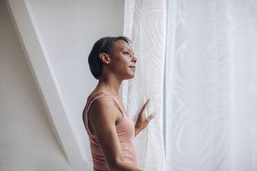 Woman at home looking out of window - SODF00049