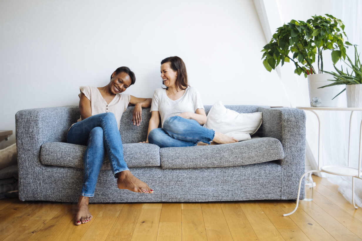 Two happy relaxed women sitting on couch at home - SODF00052 - Sofie Delauw/Westend61