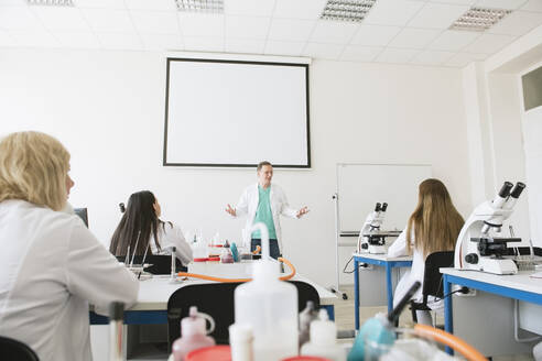 Lithuania, Vilnius, Students and teacher working in science class - AHSF00599