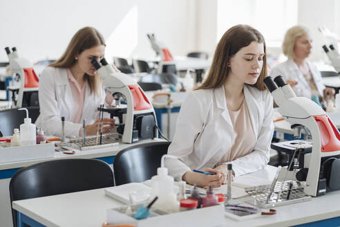 Researchers in white coats working with microscopes in lab - AHSF00659