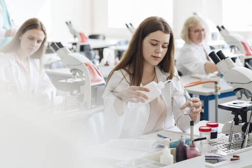 Lithuania, Vilnius, Researchers in white coats working in science class - AHSF00665