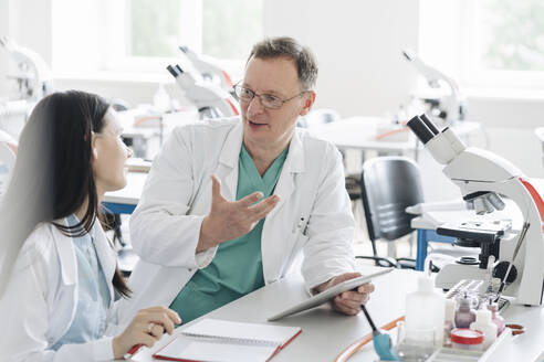 Lithuania, Vilnius, Teacher and student in white coats talking and using tablet in lab - AHSF00680