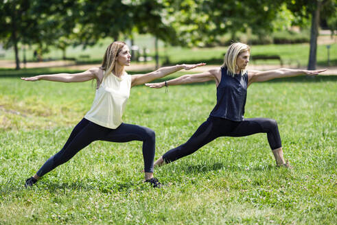 Mature woman doing yoga with her daughter in a park - JSMF01142