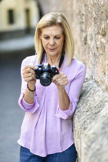 Mature woman with a SLR camera in the city - JSMF01184