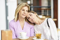 Mature woman with her daughter sitting at an outdoor table in a cafe - JSMF01193