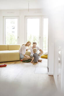 Happy family with a son playing in living room of their new home - PESF01654