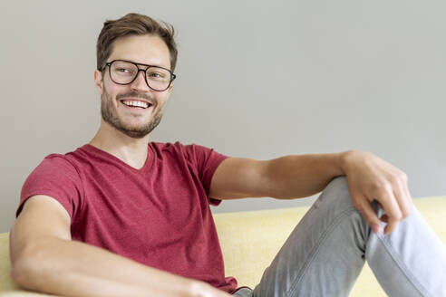 Portrait of a happy man sitting on a couch - PESF01669