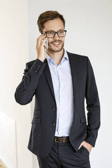 Smiling businessman talking on cell phone - PESF01687