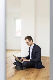Deutschland, NRW, Köln, junger MAnn mit Laptop auf dem Boden arbeitend, neue Wohnung, Businesslook - PESF01693