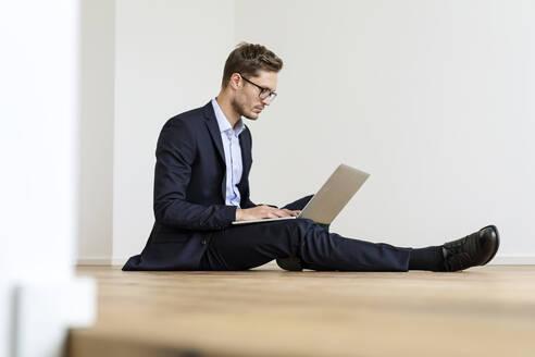 Deutschland, NRW, Köln, junger MAnn mit Laptop auf dem Boden arbeitend, neue Wohnung, Businesslook - PESF01696