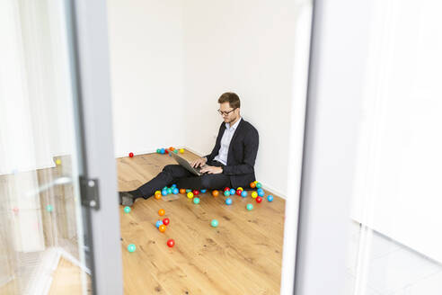 Businessman sitting on the floor using laptop surrounded by colourful balls - PESF01699