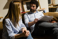 Businessman and businesswoman sitting on couch in office discussing papers - GIOF06809