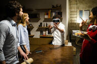 Colleagues looking at man wearing VR glasses in office - GIOF06842