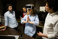 Colleagues looking at woman wearing VR glasses in office - GIOF06845