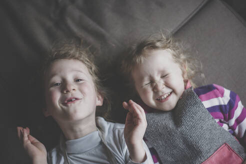 Portrait of two little sisters lying side by side on couch having fun, top view - IHF00179