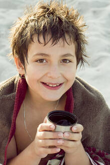 A smiling boy warming himself up after swimming with a cup of tea, Hamburg, DE - IHF00187