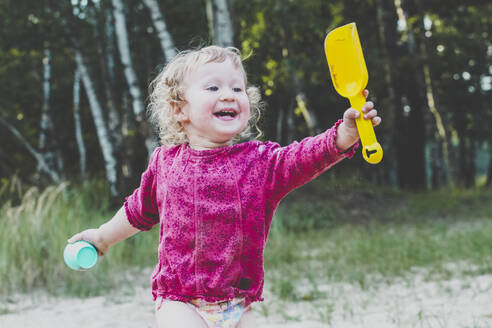 Portrait of happy toddler girl with sandbox toys - IHF00196