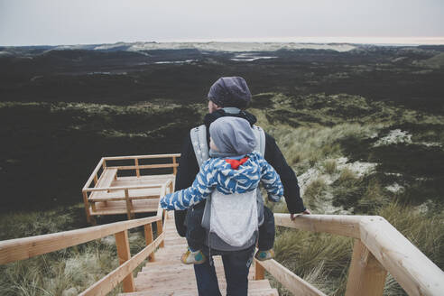 Back view of man with toddler son in baby carrier on his back in front of view terrace, Sylt, Germany - IHF00199