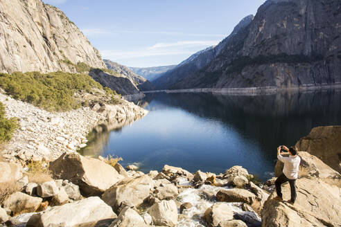 Caucasian man photographing lake in Yosemite National Park, California, United States - BLEF10618