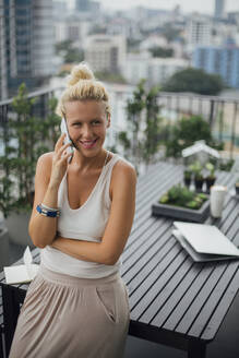 Caucasian woman talking on cell phone on balcony - BLEF10718