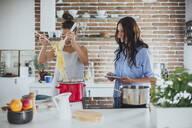 Caucasian women cooking pasta in kitchen - BLEF10754
