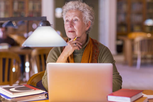 Older mixed race woman using laptop in library - BLEF10838