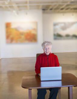 Older mixed race woman using laptop in art gallery - BLEF10844