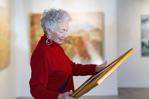 Older mixed race woman holding picture in art gallery - BLEF10850