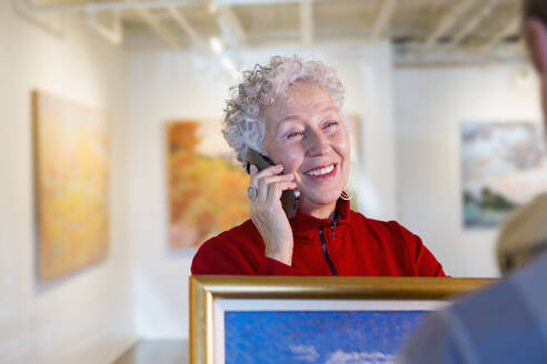 Older mixed race woman using cell phone in art gallery - BLEF10853