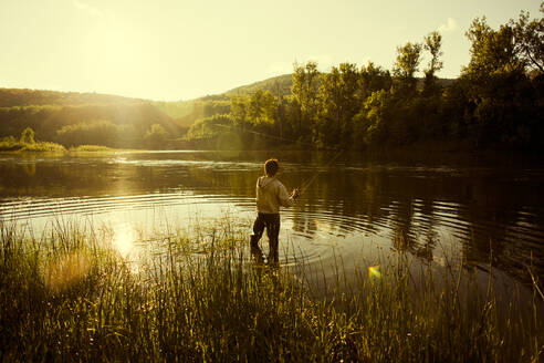 Caucasian man fishing in still lake - BLEF10907