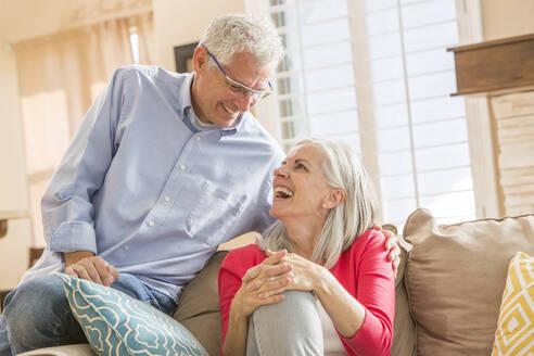 Caucasian couple sitting on sofa - BLEF10940