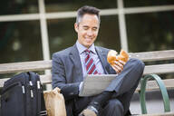 Mixed race businessman eating and using digital tablet - BLEF10961