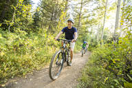 Caucasian father and children riding mountain bikes - BLEF10976