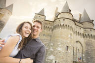 Caucasian couple smiling at castle - BLEF10991