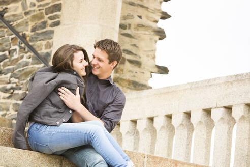Caucasian couple hugging on castle steps - BLEF10994