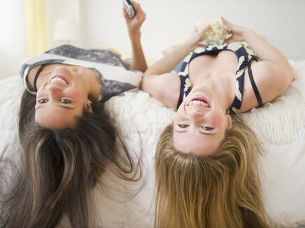 Teenage girls laying on bed upside-down - BLEF11129