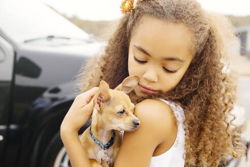 Mixed race girl petting dog outdoors - BLEF11357