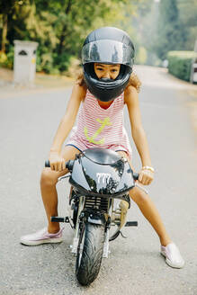 Mixed race girl sitting on miniature motorcycle - BLEF11360