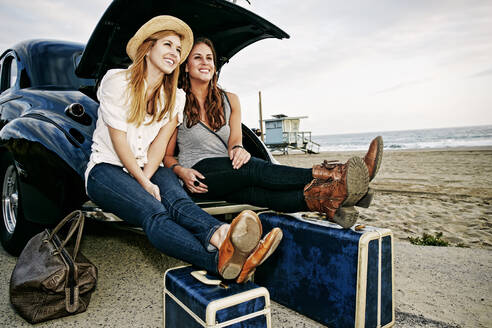 Women with luggage and vintage car on beach - BLEF11474