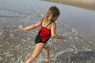 Mixed race girl splashing in waves on beach - BLEF11519