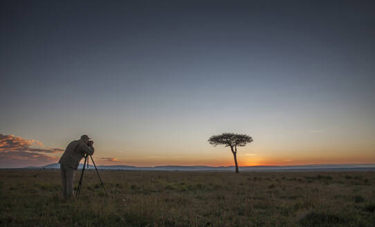Caucasian photographer photographing tree in savanna - BLEF11573