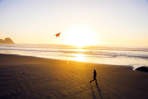 Caucasian woman flying kite on beach - BLEF11594