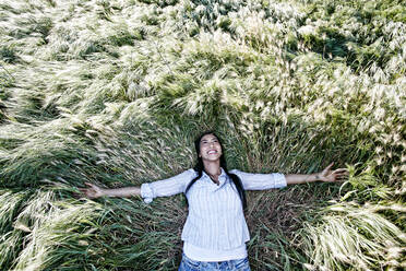 Mixed race woman laying in grass - BLEF11666