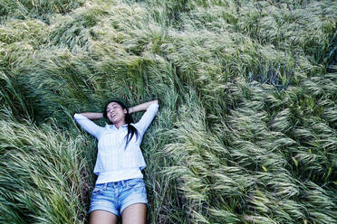Mixed race woman laying in grass - BLEF11669