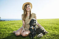 Caucasian woman sitting in field with dog - BLEF11699