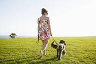 Caucasian woman walking dog in field - BLEF11708