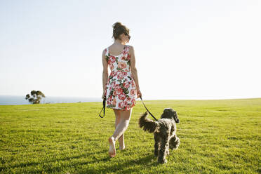 Caucasian woman walking dog in field - BLEF11708