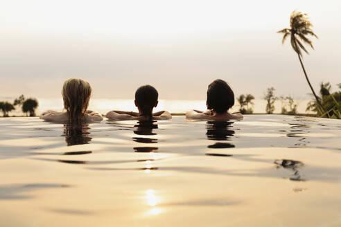 Women admiring scenic view in infinity pool - BLEF11930